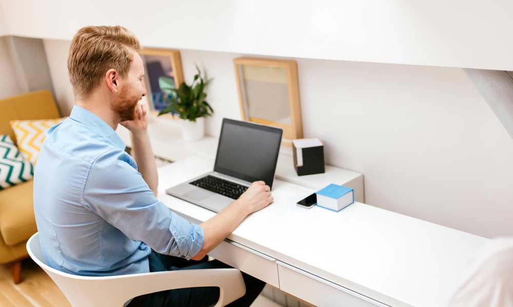man working on macbook on white table